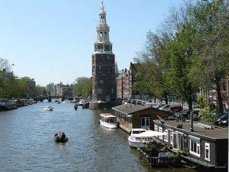 Uno de los grandes canales de Ámsterdam con una embarcación navegando