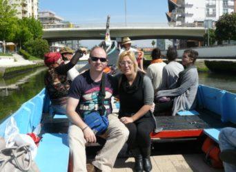 Una joven pareja de viajeros paseando en un moliceiro por Aveiro