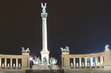Vista nocturna de parte de la hermosa plaza con sus columnas y estatuas que la decoran.