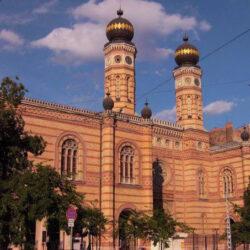 Tiene dos altas torres laterales con reloj, y sendas cúpulas características de las sinagogas.