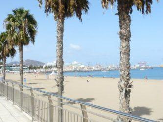 La playa vista desde el paseo marítimo con el Puerto de la Luz al fondo