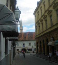 Vemos una torre de la catedral de Zagreb al fondo de esta calle